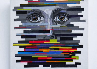 On a square white canvas there is a grey face with wide open dark blue eyes with an amber ring around the pupil. The image is distorted by a series of paper strips in shades of grey. The forehead and mouth are the most distorted and the strips here are of different widths, lengths and colours. Shades of red, green, purple, orange, yellow and blue. The edges of the artwork upon the canvas are uneven edges of the strips of paper.
