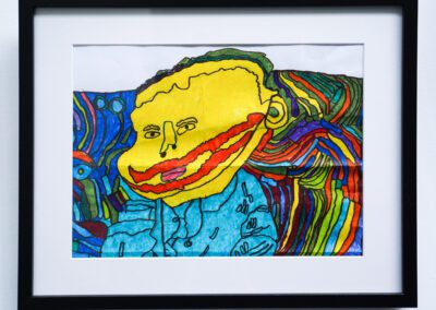 This portrait is of the artist Vincent Van Gogh. It is inspired by the bright colours and shapes he used. The piece is draw with brightly coloured felt tips. The main face of the portrait is quite abstract and is coloured in a bright yellow. The face is turned slightly to one side, but the person looks out of the picture at us. He has small eyes and a nose which are drawn in black felt tip, close together in the middle of the persons face. Under the nose is a large mouth which fills all of the bottom of the face. The lips are bright red and thick with rough, wobbly edges. Inside the lips we can just see the tip of a pink tongue sticking out. The person has a thin line of dark green hair which sits around the top of the face. The person is wearing a bright but light blue top with stitching and details on it. The background is made up of lots of small shapes some swirling upwards on the right in green, yellow, blue and orange. On the left there are circle shapes and more swirling lines in blues.